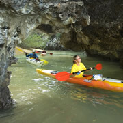 Canoeing through a cave in Phang Nga Bay